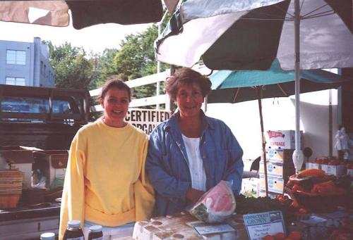 Farmer Kathy Caruso with a friend working at a farmer's market